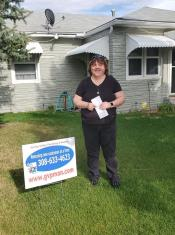 Gering Valley Plumbing & Heating Monthly Sign Winner for April, Tellina after receiving her $100 check for leaving her sign in after she called Gering Valley Plumbing & Heating for help.